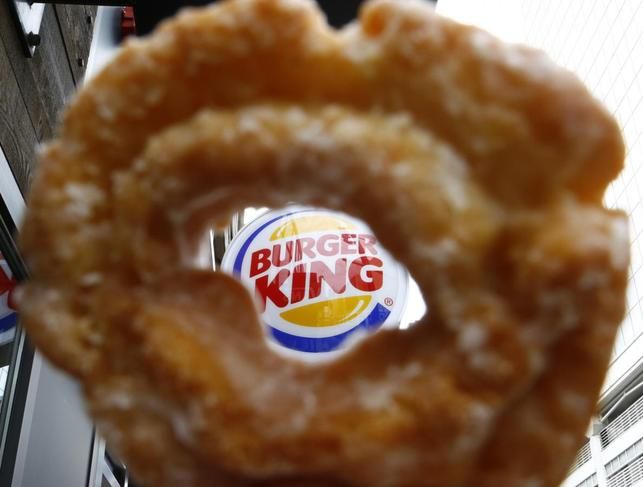 The Burger King logo is seen through a Tim Horton's doughnut hole in a photo illustration outside a restaurant in Toronto August 29, 2014. REUTERS/Chris Helgren