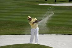 Chapchai Nirat of Thailand hits out of the bunker at the first hole during the final round of the Volvo Masters of Asia golf tournament at the Thai Country Club in Bangkok December 21, 2008. REUTERS/Sukree Sukplang