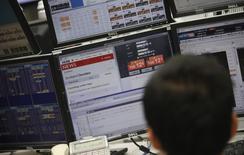 Сотрудник компании, занимающейся торговлей иностранной валютой, за работой в Токио 19 сентября 2014 года. Азиатские фондовые рынки завершили торги четверга разнонаправленно под влиянием экономических отчетов и местных факторов. REUTERS/Toru Hanai