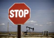 Станок-качалка на фоне дорожного знака в Феллоус, Калифорния 3 апреля 2010 года. Цены на нефть Brent продолжают снижение после падения до 26-месячного минимума в среду за счет избытка нефти на мировом рынке. REUTERS/Lucy Nicholson