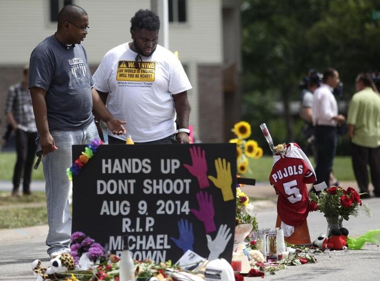 Two men stand over the makeshift memorial for Michael Brown in Ferguson, Missouri in this August 19, 2014 file photo.  REUTERS/Joshua Lott/Files