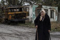 Женщина у сгоревшего грузовика в Иловайске 25 сентября 2014 года. Трехсторонняя группа в составе представителей Украины, России и ОБСЕ в пятницу начала работу по определению границ 30-километровой буферной зоны в районе боев армии с пророссийскими сепаратистами на востоке Украины. REUTERS/Marko Djurica