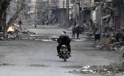 Una pareja conduce una motocicleta en una calle con escombros de edificios dañados en Deir al-Zor. Imagen de archivo, 05 marzo, 2014. Ataques aéreos y con misiles que habrían sido llevados a cabo por las fuerzas lideradas por Estados Unidos alcanzaron durante la noche y en la madrugada del viernes yacimientos petroleros y bases del Estado Islámico en la provincia de Deir al-Zor, en el este de Siria, dijo un grupo de seguimiento. REUTERS/Stringer