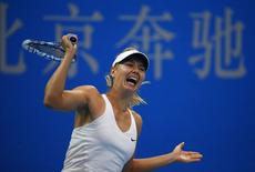 Maria Sharapova of Russia returns the ball during her women's singles match against Kaia Kanepi of Estonia at the China Open tennis tournament in Beijing September 28, 2014. REUTERS/Petar Kujundzic