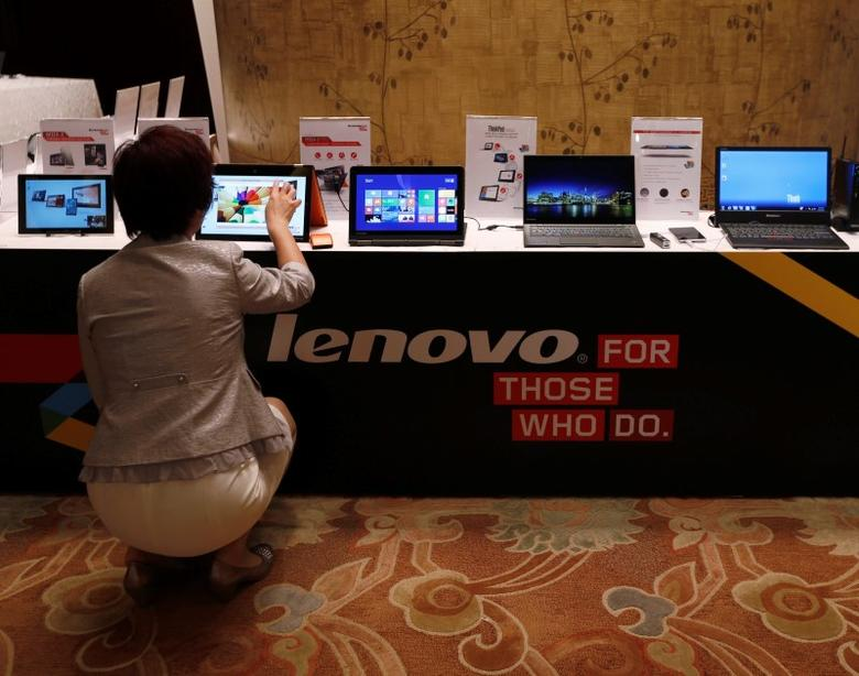 A woman tries a Lenovo tablet on display during a news conference announcing the company's annual results in Hong Kong May 21, 2014.  REUTERS/Bobby Yip