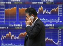 Un hombre pasa frente a una pantalla electrónica que muestra el índice Nikkei en Tokio. Imagen de archivo, 25 septiembre, 2014.  El índice Nikkei de la bolsa de Tokio subió el lunes luego de que la debilidad del yen apoyó la confianza, mientras que la toma de riesgo fue impulsada por unos datos reportados el viernes que mostraron que la economía estadounidense creció en el segundo trimestre a su ritmo más acelerado en dos años y medio. REUTERS/Toru Hanai