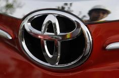 A worker is reflected next to the emblem of a Toyota Vios sedan at a stockyard of the Toyota Philippines manufacturing plant in Sta Rosa, Laguna, south of Manila August 11, 2014.  REUTERS/Erik De Castro