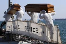 Coffins containing bodies of migrants who died are carried off a navy ship at the Sicilian harbour of Augusta August 26, 2014.   REUTERS/Antonio Parrinello