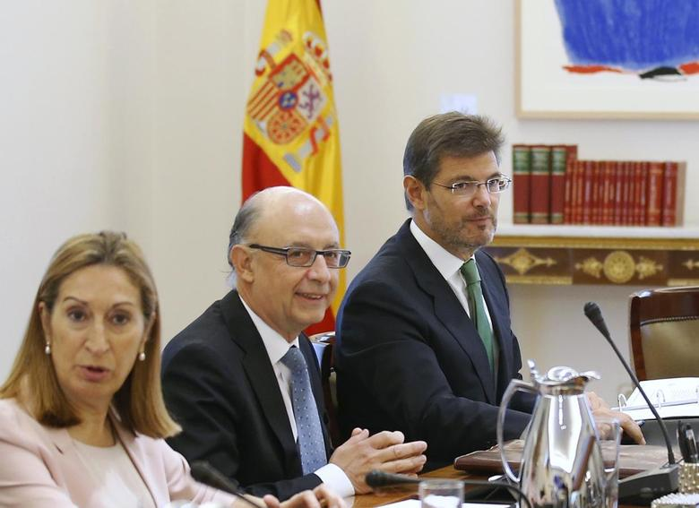 Spain's new Justice Minister Rafael Catala (R) sits next to Spain's Treasury and Public Administration Minister Cristobal Montoro (C) and Public Works Minister Ana Pastor during his first cabinet meeting at Moncloa palace in Madrid September 29, 2014.  REUTERS/Andrea Comas
