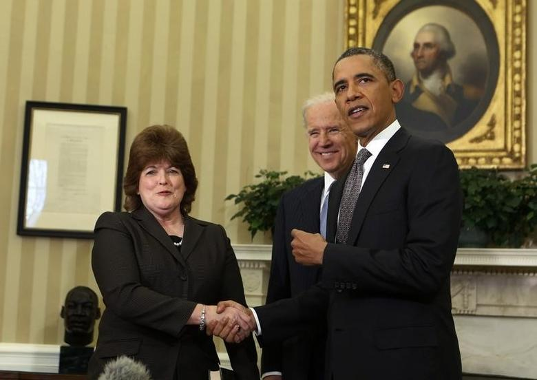 U.S. President Barack Obama (R) shakes hands with U.S. Secret Service agent Julia Pierson (L) after she is sworn in as the first woman Director of the Secret Service by Vice President Joe Biden in the Oval Office of the White House in Washington, March 27, 2013.   REUTERS/Larry Downing