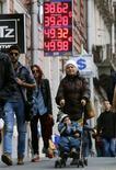 Люди проходят мимо пункта обмена валюты в Санкт-Петербурге 26 сентября 2014 года. Рубль во вторник показывает положительную динамику к евро, ускорившуюся после обвала единой валюты на мировых рынках, и относительно стабилен в паре с долларом, взяв передышку после падения накануне к абсолютным минимумам в условиях локального дефицита валюты, западных санкций, дешевой нефти и глобального спроса на американскую валюту. REUTERS/Alexander Demianchuk