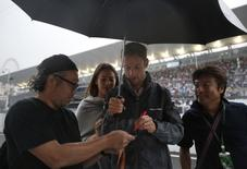 McLaren Formula One driver Jenson Button of Britain, with Jessica Michibata, signs autographs for fans at the Suzuka circuit in Suzuka, western Japan, October 2, 2014, ahead of Sunday's Japanese F1 Grand Prix. REUTERS/Yuya Shino