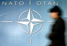 Женщина проходит мимо логотипа НАТО у входа в штаб-квартиру альянса в Брюсселе 4 декабря 2003 года. Сотни российских военнослужащих, включая спецназовцев, остаются на территории Украины, а вблизи российско-украинской границы сосредоточены около 20.000 солдат, заявил в четверг представитель НАТО.  Thierry Roge/Reuters