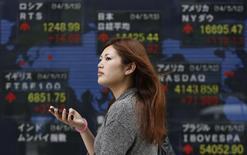 Прохожая у брокерской конторы в Токио 13 мая 2014 года. Японский фондовый рынок вырос за неделю, а рынок Гонконга снизился. REUTERS/Yuya Shino