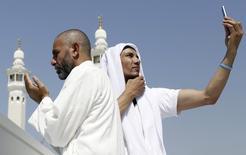 La mode des selfies, qui fait rage sur les réseaux sociaux, n'épargne par le grand pèlerinage annuel de La Mecque, en Arabie saoudite. Certains dignitaires religieux considèrent que les pèlerins devraient plutôt se concentrer sur la prière, mais d'autres jugent cette pratique inoffensive et totalement conciliable avec les principes de l'islam. /Photo d'archives/REUTERS/Amr Abdallah Dalsh