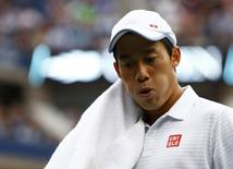 Kei Nishikori of Japan wipes his neck during the men's singles final match against Marin Cilic of Croatia at the 2014 U.S. Open tennis tournament in New York, September 8, 2014.      REUTERS/Adam Hunger