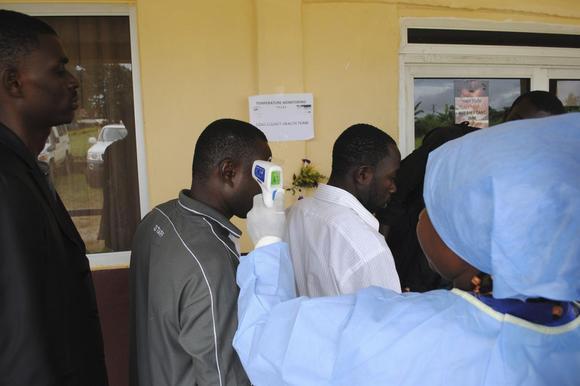Um profissional de saúde mede a temperatura das pessoas em uma coletiva de imprensa sobre a abertura de uma nova clínica Ebola, fora Monrovia 3 de outubro de 2014 REUTERS / James Giahyue