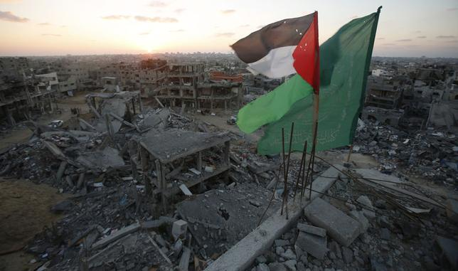 A Palestinian flag and a Hamas flag (R) flutter atop the wreckage of a house, which witnesses said was destroyed during the seven-week Israeli offensive, in the east of Gaza City September 3, 2014.   REUTERS/Suhaib Salem