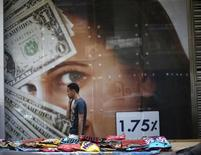 Пешеход проходит мимо пункта обмена валюты в Каире 29 мая 2014 года. Курс доллара вернулся к росту после спада накануне. REUTERS/Amr Abdallah Dalsh