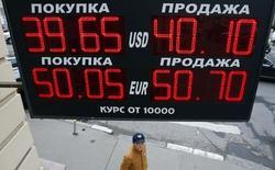 """Мальчик проходит мимо вывески пункта обмена валюты в Москве 7 октября 2014 года. Рубль во вторник днем возобновил снижение после краткой паузы, связанной с повсеместной фиксацией прибыли в """"длинном"""" долларе; текущее восстановление валюты США на мировых рынках и перманентный внутренний спрос на неё вновь вывели бивалютную корзину к верхней границе плавающего коридора ЦБ, где регулятор проводит неограниченные интервенции. REUTERS/Sergei Karpukhin"""