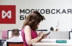 Женщина пользуется телефоном в помещении Московской биржи 3 июня 2014 года. Российский фондовый рынок корректируется вторую сессию, и биржевые индексы практически нивелировали бодрый рост понедельника на фоне стремления нефтяных фьючерсов к многолетним минимумам и снижения других активов на зарубежных площадках. REUTERS/Sergei Karpukhin