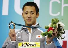Gold medallist Naoya Tomita of Japan poses after the men's 200m breaststroke final at the 10th FINA World Swimming Championships (25m) in Dubai in this December 17, 2010 file photo. REUTERS/Rabih El Moghrabi