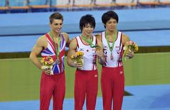(From L to R) Silver medalist Max Whitlock of Britain, gold medalist Kohei Uchimura of Japan and bronze medalist Yusuke Tanaka of Japan pose for photographs at the podium after the men's all-around final of the 2014 World Artistic Gymnastics Championships in Nanning, Guangxi Zhuang Autonomous Region, October 9, 2014. REUTERS/Stringer