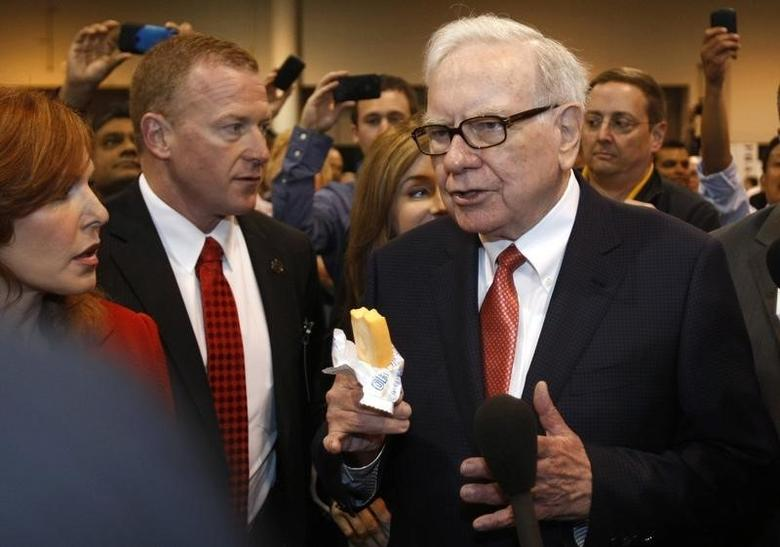 Berkshire Hathaway Chairman Warren Buffett holds a Dairy Queen ice cream bar and answers reporters' questions as his wanders the company trade show before the Berkshire Hathaway annual meeting in Omaha, Nebraska April 30, 2011. REUTERS/Rick Wilking