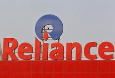 A crow sits a Reliance logo installed on its mart in the western Indian city of Ahmedabad January 17, 2014. REUTERS/Amit Dave
