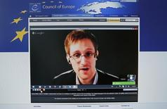 "Accused government whistleblower Edward Snowden is seen on the computer screen of a journalist on the internet site of the Council of Europe, as he speaks via video conference with members of the Committee on legal Affairs and Human Rights of the Parliamentary Assembly of the Council of Europe during an hearing on ""mass surveillance"" in Strasbourg, April 8, 2014. REUTERS/Vincent Kessler"