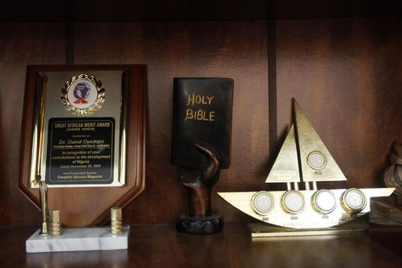 A mini sculpture in the shape of the Bible is displayed next to an award (L) for Bishop David Oyedepo, founder of the Living Faith Church, also known as the Winners' Chapel, recognising him his contribution to the development of Nigeria, in his office in Ota district, Ogun state, some 60 km (37 miles) outside Nigeria's commercial capital Lagos September 28, 2014. REUTERS-Akintunde Akinleye