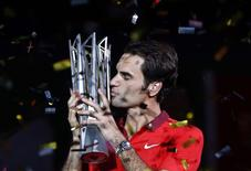 Roger Federer of Switzerland kisses the trophy after winning the men's singles final match against Gilles Simon of France at the Shanghai Masters tennis tournament in Shanghai October 12, 2014. REUTERS/Aly Song