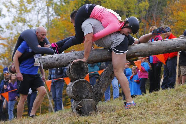 10月11日、米メーン州西部のスキーリゾート地で男性が女性を背負って泥水の中などを走る障害物走「妻担ぎ競争」の北米大会が開催された(2014年 ロイター/Brian Snyder)