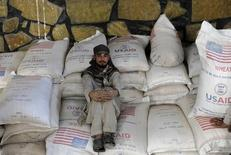 An Afghan worker rests after unloading sacks of wheat which will be distributed to Afghan widows for their monthly rations from the World Food Program (WFP) in Kabul October 26, 2010. REUTERS/Omar Sobhani