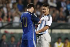 Atacante da Argentina Lionel Messi autografa camisa de torcedor que invadiu campo durante amistoso contra Hong Kong, em Hong Kong. 14/10/2014 REUTERS/Tyrone Siu