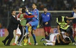 Fans and players of Serbia and Albania scuffle during their Euro 2016 Group I qualifying soccer match at the FK Partizan stadium in Belgrade October 14, 2014.  REUTERS/Marko Djurica