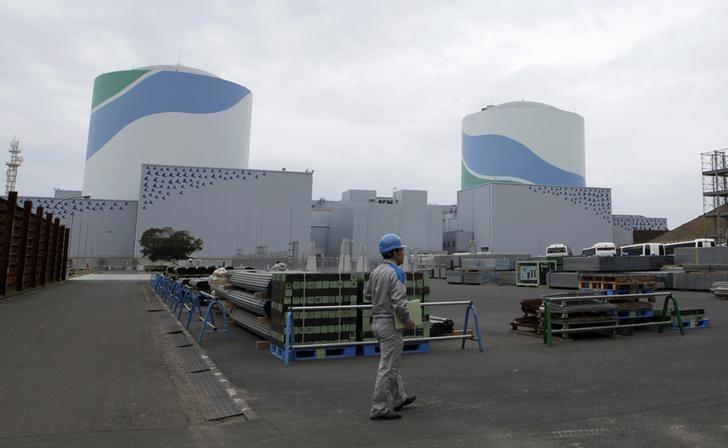 An employee of Kyushu Electric Power Co walks in front of reactor buildings at the company's Sendai nuclear power plant in Satsumasendai, Kagoshima prefecture April 3, 2014. REUTERS/Mari Saito
