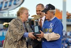 Oct 15, 2014; Kansas City, MO, USA; Kansas City Royals owner David Glass (right) is presented with the American League championship trophy after game four of the 2014 ALCS playoff baseball game against the Baltimore Orioles at Kauffman Stadium. The Royals swept the Orioles to advance to the World Series. Mandatory Credit: Denny Medley-USA TODAY Sports