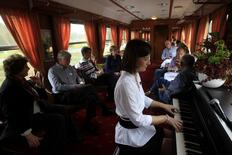 Passengers enjoy piano music in the bar car of a historic Tehran-bound train as it leaves Budapest October 15, 2014. REUTERS/Bernadett Szabo