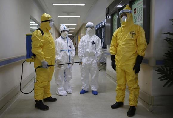 Health workers in protection suits wait in the corridor near a quarantine ward during a drill to demonstrate the procedures of handling Ebola victims, at a hospital in Guangzhou, Guangdong province October 16, 2014. REUTERS/Stringer