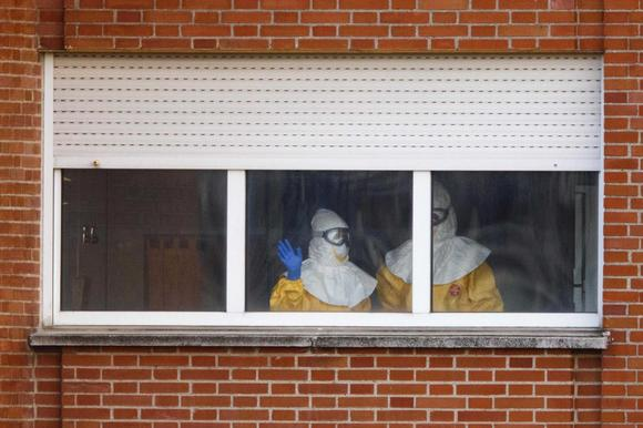 Health workers in protective suits stand near a window at an isolation ward on the sixth floor of Madrid's Carlos III Hospital October 12, 2014. REUTERS/Paul Hanna