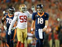 San Francisco 49ers linebacker Aaron Lynch (59) congratulates Denver Broncos quarterback Peyton Manning (18) after his 509th touchdown pass in the second quarter at Sports Authority Field at Mile High. Ron Chenoy-USA TODAY Sports