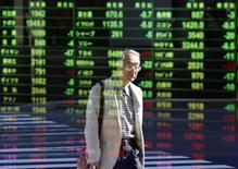 Экран брокерской конторы в Токио 17 октября 2014 года. Азиатские фондовые рынки выросли в понедельник благодаря улучшению макроэкономической статистики США. REUTERS/Yuya Shino
