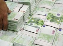 Пачки купюр по 100 евро в штаб-квартире GSA Austria (Money Service Austria) в Вене 22 июля 2013 года. Европейский центробанк начал скупать обеспеченные облигации, сообщил представитель банка в понедельник, открыв новый фронт в борьбе за оживление экономики еврозоны и предотвращение дефляции. REUTERS/Leonhard Foeger