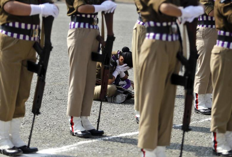 A member of a female Indian police contingent holds her face in her hands as she sits during a parade to mark Police Commemoration Day in Zewan, on the outskirts of Srinagar, October 21, 2014.  REUTERS/Danish Ismail