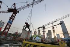 Operário trabalha em um canteiro de obras no bairro financeiro da região central de Pequim. A China cresceu no terceiro trimestre no ritmo mais fraco desde a crise financeira global. A retomada na produção industrial e a confiança do governo de que o mercado de trabalho continua estável foram compensados por mais desaceleração no setor imobiliário. 21/10/2014. REUTERS/Jason Lee