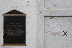 A plaque, pennies, and scratched X's adorn the reputed tomb of voodoo queen Marie Laveau in the St. Louis Cemetary in New Orleans, in a file photo. REUTERS/Lucas Jackson