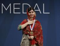 Malala Yousafzai, of Pakistan, gestures as she wears the 2014 Liberty Medal which was presented to her at a ceremony at the National Constitution Center in Philadelphia October 21, 2014. REUTERS/Tom Mihalek