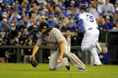 San Francisco Giants starting pitcher Madison Bumgarner (front) slides to field a ball hit by Kansas City Royals first baseman Eric Hosmer (35) in the 6th inning during game one of the 2014 World Series at Kauffman Stadium. John Rieger-USA TODAY Sports