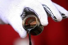 Президент Венесуэлы Уго Чавес держит баночку с нефтью во время телеэфира  17 февраля 2008 года. Расширение западных санкций, дальнейшее снижение цен на нефть и ослабление российской экономики вкупе с непредсказуемой политикой властей оказывают давление на оценку кредитоспособности России, полагает международное рейтинговое агентство Moody's. REUTERS/Miraflores Palace/Handout